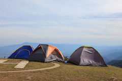 Camping tent site on top of mountain field with cloudy sky capy Royalty Free Stock Image