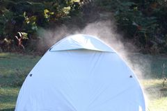 Camping tent with smoke. Camping tent coming out of smoke from the ceiling in cold weather, in nature royalty free stock photo