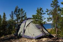 Camping tent standing on beautiful lake coastline. Karelia, Russia