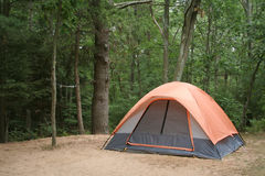 Camping Tent in Woods. Orange tent pitched on sandy campsite against background of trees. Horizontal format Stock Photo