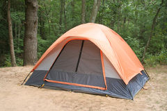 Camping Tent in Woods. Medium view of orange tent pitched on sandy campsite against background of trees. Horizontal format Stock Image