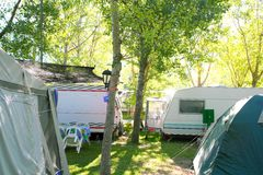 Camping tents caravan in green trees outdoor Stock Photography