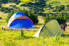 Camping Tents in the mountains. Camping green and blue tents in the mountain, adventure background Royalty Free Stock Image
