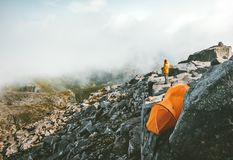 Camping on the top of mountain tent on rocky cliff. And traveler alone enjoying landscape aerial view adventure Travel hiking vacations Royalty Free Stock Photo