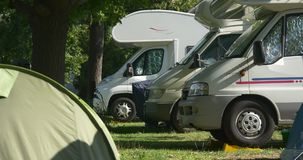 Camping trailers and a tent. Camping caravans and a tent outdoors stock footage