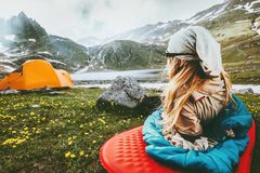Camping travel vacations woman relaxing in sleeping bag on mat. Enjoying mountains landscape Lifestyle concept adventure weekend outdoor harmony with nature Royalty Free Stock Image