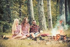 Camping travel and wanderlust. Bearded man and women smile at bonfire. Happy friends at campfire. Hipster in palid shirt royalty free stock photography