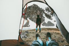 Camping traveling couple view from tent entrance. Women walking in mountains men feet relaxing inside Lifestyle concept adventure vacations outdoor Royalty Free Stock Photos