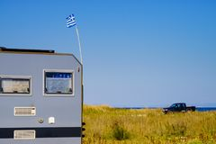 Camping truck with Greek flag. Camping truck on beach with Greek national flag on roof. Traveling, adventure concept Royalty Free Stock Image