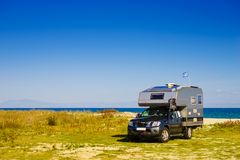 Camping truck with Greek flag. Camping truck on beach with Greek national flag on roof. Traveling, adventure concept Stock Image