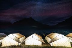 Camping under colourful sky full of stars. Glowing tents with silhouette mountains and sky full of star at Rangdum Monastery in In. Camping under colourful sky stock photography