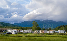 Camping under the mountains, Norway. Big camping field with lots of camper vans, mountain background and beautiful clouds. Traditional Norway outdoor landscape Stock Photos
