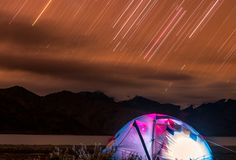 Camping under the star trails stock image