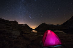 Camping under starry sky and Milky Way arc at high altitude on the italian french Alps. Glowing tent in the foreground. Adventure. Into the wild Stock Image