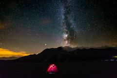 Camping under starry sky and milky way at high altitude on the Alps. Illuminated tent in the foreground. Mars Planet on the left. royalty free stock photo