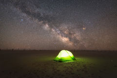 Camping under the stars. A lone camper in a lit up tent under the Milky Way Galaxy Stock Photos