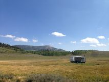 Camping in the Utah mountains. A camper sits in the meadow of the Rocky Mountains Stock Photo