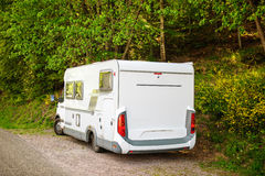 Camping van microbus parked in green forest. On a warm summer day royalty free stock photography