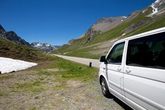 A camping van in the swiss mountains. A camping van on the side of a summit road in the swiss mountains. It looks like a beautiful road trip Royalty Free Stock Photography