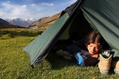 Camping in the wild. Young woman sleeping in tent in the mountains Royalty Free Stock Images