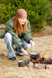Camping woman cook food fire nature Stock Image