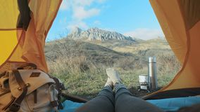 Camping woman lying in tent Close up of Girl feet wearing hiking boots relaxing on vacation. From the tent view of the