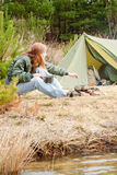 Camping woman tent cook food fire nature. Camping happy woman cook food fire tent nature water stream royalty free stock photography