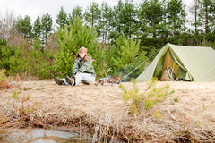 Camping woman tent sitting fire nature Royalty Free Stock Photos