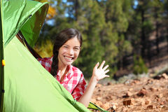Camping woman waving hello from tent Stock Photo