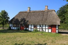 Striking wooden house at the countryside in Denmark in the summer. Camping with the wooden building with thatched roof is standing and a water pump at the stock photo