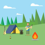 Camping in the woods.Man holding a guitar in his hands. Camping in the woods.Next to the tent is a fire, a backpack, a guitar and lamp Royalty Free Stock Images