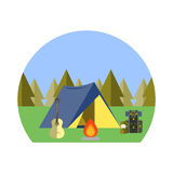 Camping in the woods. Next to the tent is a backpack, a guitar and lamp Stock Photo