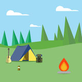 Camping in the woods. Next to the tent is a fire, a backpack, a guitar and lamp Royalty Free Stock Photos