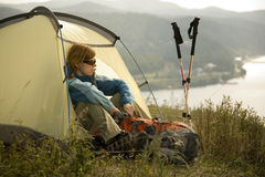 Camping. XL size. Woman hiker sitting in tent with backpack. XL size Stock Photo