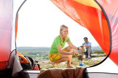 Camping young couple outside tent cook meal Royalty Free Stock Photos
