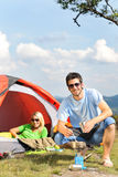 Camping young couple with tent cook countryside. Happy camping couple with tent backpack cooking in sunny countryside royalty free stock images