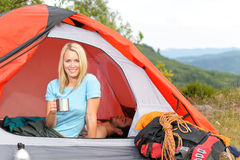Camping young woman drink mug sunset tent Stock Photos