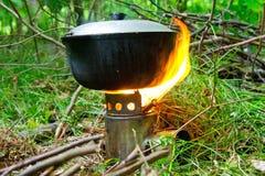 Campingowa kuchenka z ogieniem i garnkiem przygotowany jedzenie przeciw tłu wiosna zielenieje fotografia royalty free