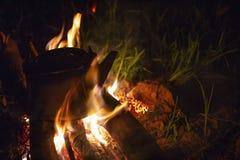 Campingowy czajnik na ogieniu przy plenerowym campsite czajnikiem dla kawy podczas gdy campin fotografia royalty free