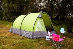 Campingplats och tent i ett fält Fotografering för Bildbyråer