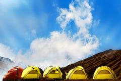 Campingplatz in den Bergen Viele gelben roten Zelte ADN gegen den blauen Himmel mit erstaunlichen Wolken Lizenzfreie Stockfotos