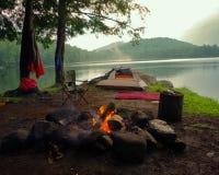 Campingplatz mit einem Zelt, einem Stuhl, einer Decke, einem Stuhl und einem Lagerfeuer in der Adirondack-Gebirgswildnis Stockfotografie