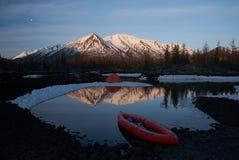 Campingplatz mit orange Zelt und Kanu auf einem See lizenzfreie stockfotografie