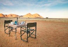 Campingtisch und Stühle in der Wüste Große Ansicht SONNENAUFGANG Stockfotos
