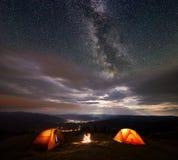 Campingzelt auf Berg nachts unter sehr sternenklarem Himmel gegen leuchtende Stadt Stockfoto