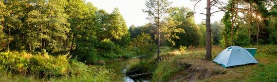 Campingzelt durch Fluss im Wald Stockfotografie