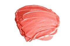 Campione del prodotto cosmetico Colpi dell'evidenziatore nel colore di corallo d'avanguardia fotografia stock libera da diritti