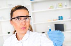 Campione di prova della donna del chimico di liquido dentro Immagini Stock