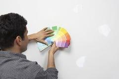 Campioni di colore della pittura della tenuta dell'uomo contro la parete Fotografia Stock Libera da Diritti