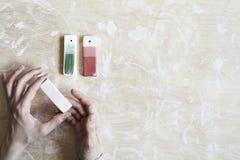 Campioni di smalto colorato per colore ceramico in mani, processo di lavoro in studio, argilla, legno, mestiere immagine stock libera da diritti